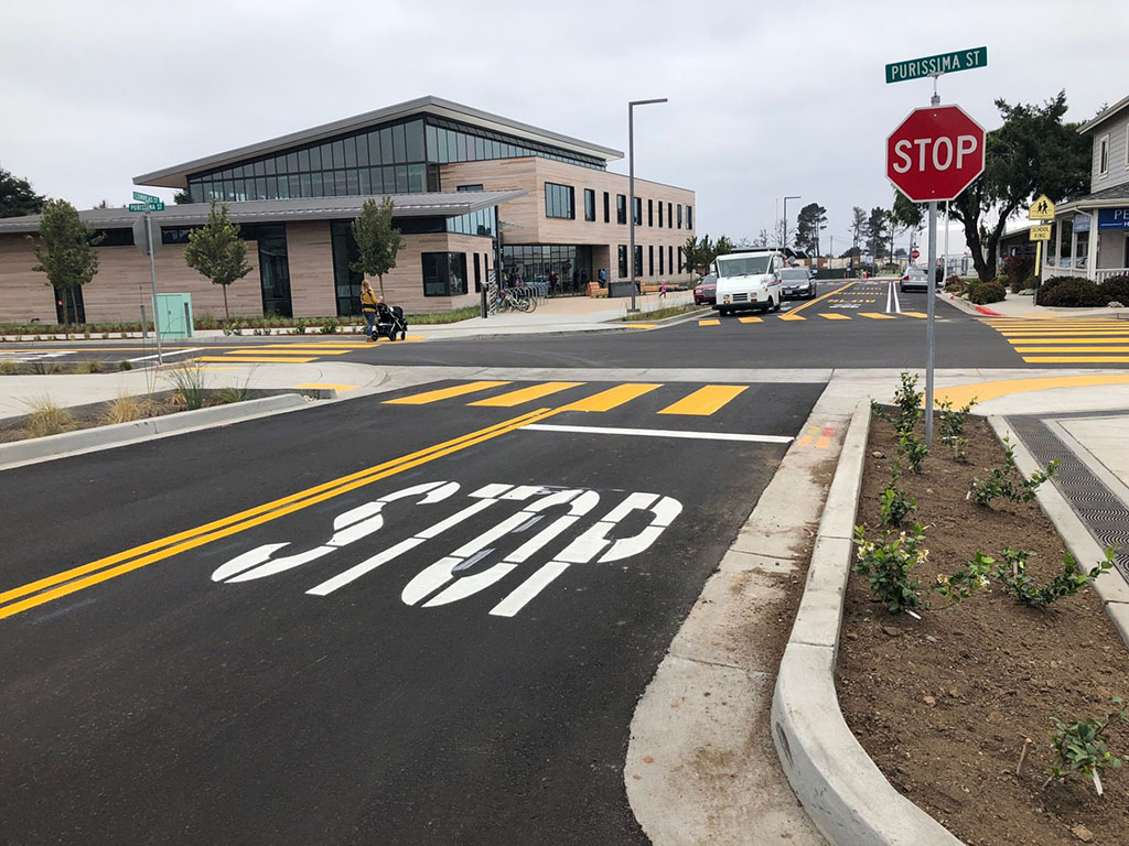 """Street with fresh-painted cross walk and the word """"stop"""" on the street; next to the street is a green infrastructure element with dirt and plants between concrete to capture and clean stormwater runoff"""